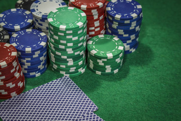 Poker chips and cards on the green table