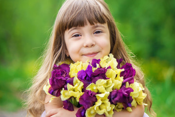 Girl with a bouquet of irises. Selective focus.