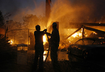 Residents help with garden hoses as a neighbor's home burns to the ground in Yorba Linda, California