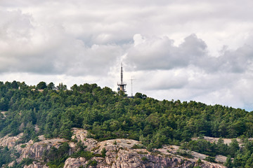 Radio communication tower rising up through the trees in the woods on the cliffs in Stavanger, Norway