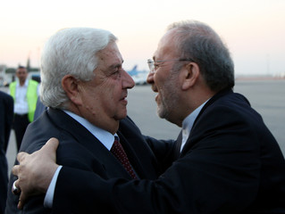 Iranian FM Mottaki embraces Syrian counterpart al-Moualem upon his arrival in Damascus