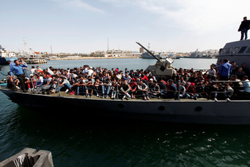 Illegal migrants arrive by boat at a naval base after they were rescued by Libyan coastguard in the coastal city of Tripoli