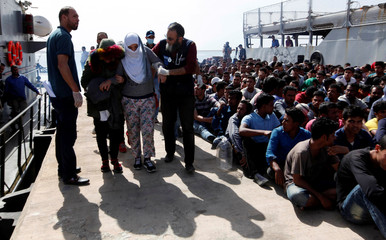 Illegal migrants arrive at a naval base after they were rescued by Libyan coastguard in the coastal city of Tripoli