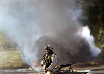 A U.S. ARMY SOLDIER SECURES THE AREA WHILE SMOKE AND FIRE RISE FROM AU.S. ARMY APC AFTER AN ATTACK IN ...
