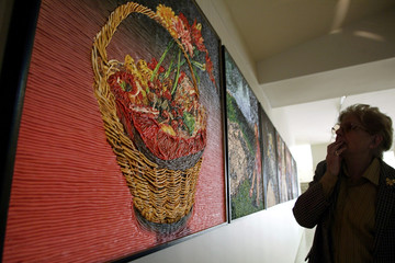 A woman looks at a work of art made of plasticine on wood at an art gallery in Buenos Aires.