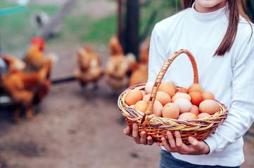 the girl holds a basket full of fresh chicken eggs.