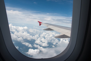 When looking through the window while on a plane. You can see the sky and clouds of airplane wings. - Concept clouds, plane, sky.