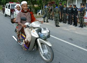 THAI MUSLIM COUPLE RIDE PAST TROOPS IN YALA, THAILAND.