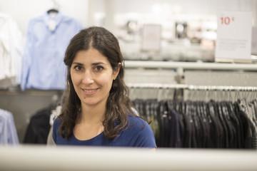 Woman buying clotes in mall looking at camera