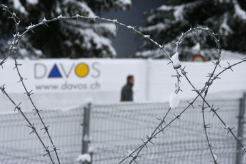 The venue of the World Economic Forum is seen through snow-covered barbed wire in the Swiss Alpine resort town of Davos