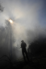 An Israeli fireman extinguishes fire after a rocket, fired by Palestinian militants in Gaza, landed at a nature reserve near Kibbutz Carmia