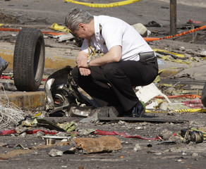 A naval officer inspects the scene of a plane crash in Mexico City