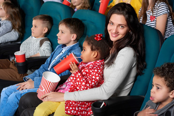 Cheerful young woman smiling to the camera happily with her little daughter sitting on her lap enjoying a movie at the cinema together family lifestyle leisure enjoyment happiness comedy cartoons.