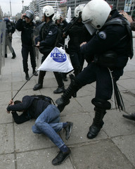 Riot police beat a demonstrator as he and many others tried to walk towards the parliament building in central Ankara