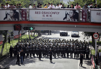 Chinese security forces block a main road during a demonstration by Han Chinese at the center of Urumqi