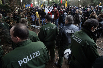 German riot police line up in front of protestors during a demonstration against the clearing of a huge wood area for a new runway for the airport in Frankfurt