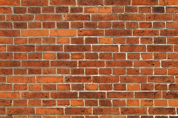 Wall of bright red brick with white seams