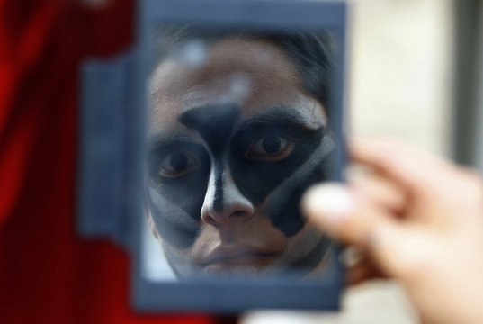 A dancer from Peru's Jallmay dance company applies make-up during the 'Ciudad de Burgos' in Burgos