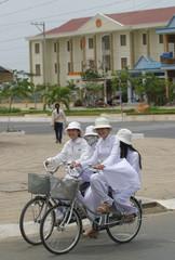 Vietnamese school girls ride past communist People's Court in Vung Tau, Vietnam