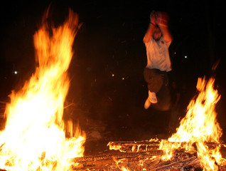 Iranian man jumps over a fire to mark the last Tuesday of the Iranian calendar year in Tehran