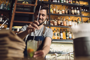 Young male bartender preparing an alcohol cocktail