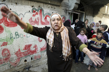 Palestinian woman shouts after shells fired by Israeli naval boat landed in Gaza