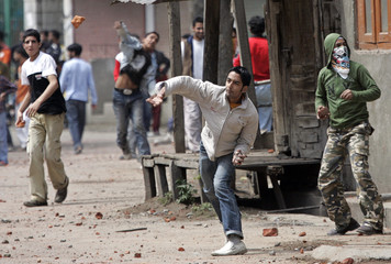 Kashmiri Muslim youths throw stones and pieces of bricks towards Indian policemen in Srinagar