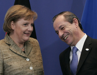 Malta's PM Gonzi is welcomed by German Chancellor Merkel at a two-day EU leaders summit in Brussels