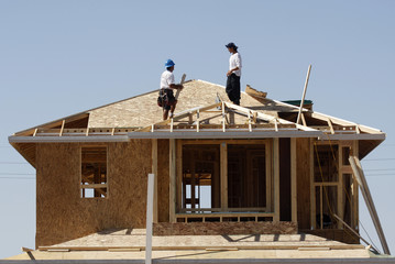 Workers construct a house by developer KB Home in Gilbert, Arizona