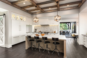 Beautiful Kitchen in New Luxury Home with Island, Cross Hatch Wood Beams on Ceiling, Hardwood Floors, Farmhouse Sink, and Elegant Pendant Lights. Open Doors in Background Lead to Outdoor Patio
