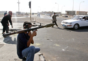 Iraqi militiamen control traffic in Basra.