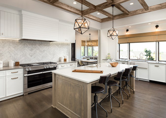 Beautiful Kitchen in New Luxury Home with Island, Cross Hatch Wood Beams on Ceiling, Hardwood Floors, Farmhouse Sink, and Elegant Pendant Lights