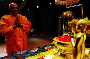 A MONK PRAYS IN FRONT OF THE ASHES OF BUDDHA.