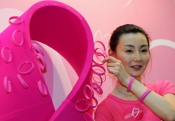 Hong Kong actress Maggie Cheung poses with a pink ribbon, a global symbol for breast cancer awarenes..
