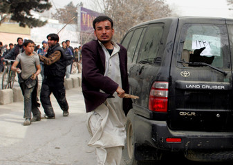 An Afghan protester breaks the window of a vehicle in Kabul