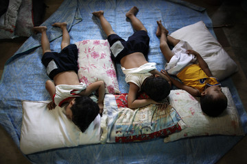 Children sleep inside an evacuation center for victims hit by floods caused by Typhoon Ketsana, locally known as Ondoy, in the town of Taytay