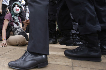 A demonstrator sits in protest against Governor Arruda during a police repossession operation in Brasilia
