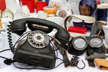 Flohmarkt Angebot mit altem Telefon mit Wählscheibe, Taucherbrille und Keramik