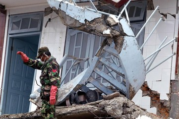 An Indonesian military personnel moves through the rubble on Indonesia's Nias island.