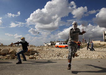 Palestinians use sling to throw stones during protest in Nilin