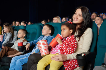 Young beautiful woman smiling holding her young daughter on the lap enjoying movie premiere at the cinema copyspace happiness living people leisure activity weekend togetherness concept.