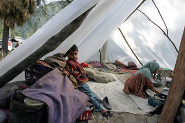 Kashmiri woman cooks in a makeshift shelter outside her destroyed home in Karnah