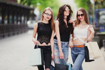Three girls with shopping bags on park