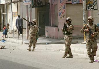 Iraqi soldiers patrol a street in Diwaniya