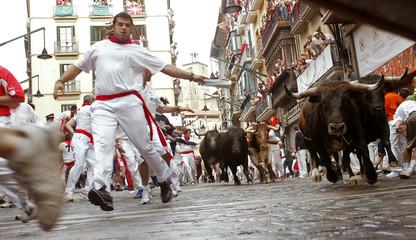 Runners lead bulls during third running of bulls in Pamplona