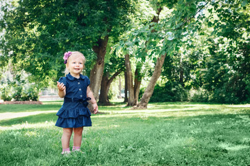 Portrait of cute adorable little Caucasian girl child in blue dress standing in field meadow park outside, making soap  bubbles, lifestyle childhood