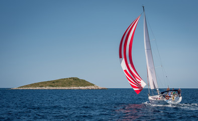 Sailing boat with spinnaker approaching small island in Croatia