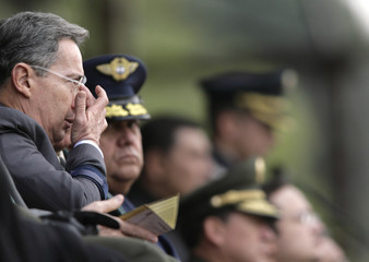 Colombia's President Uribe adjusts his glasses during a police ceremony at the General Santander's Academy in Bogota
