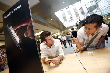 B.Q. Nguyen takes a photo of Jason Rappaport with the new iPhone inside the Apple Store in New York