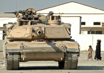 Iraqi woman carries a bag of food past a U.S. Army Abrams tank maintaining a cordon in Najaf.